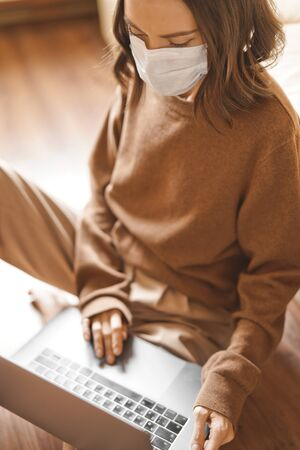 Lifestyle portrait of young lady working at notebook with mask. Woman concept for alternative office freelance. Stay home. Coronavirus. Quarantine. Online training education and freelance work. Coronavirus pandemic in the world