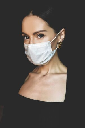 Lifestyle portrait of young beautiful lady with medical mask. Stay home. Coronavirus. Quarantine. Coronavirus pandemic in the world Banco de Imagens