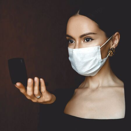 Lifestyle portrait of young beautiful lady in medical mask looking in a compact mirror. Stay home. Coronavirus. Quarantine. Coronavirus pandemic in the world