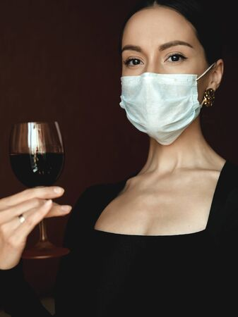 Lifestyle portrait of young beautiful lady in medical mask with glass of vine. Stay home. Coronavirus. Quarantine. Coronavirus pandemic in the world