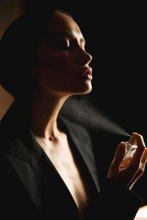 Athmospheric photo of sensual lady spraying perfume. Beauty and Fashion. Fragrance