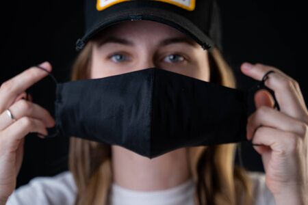 The girl puts a protective black mask on her face to protect her from the coronavirus. Coronavirus pandemic, covid-2019