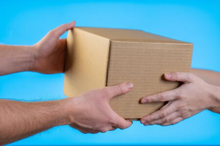 Two hands taking a box gift on blue background