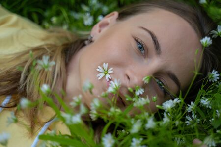 Beautiful young woman lying on the grass against the background of flowers in the forest Standard-Bild