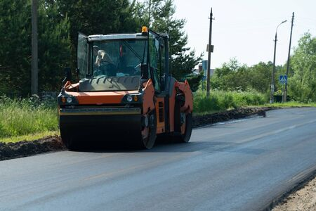 The large working machine of the skating rink makes a new asphalt. Road repair. Close-up Stockfoto