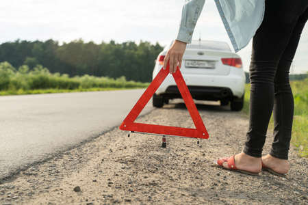 Stressed woman putting emergency sign on the road. Woman having problems with car, stopped her vehicle on the roadside and waits for help