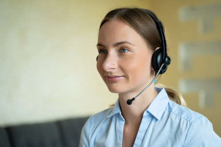 Businesswoman talking on the phone while working on her computer at the office. Call сenter agent working on hotline