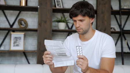 Man with medicine and pills. Ill man looking at medication explanation before taking prescription drugs. Banque d'images