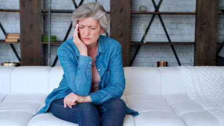 Older woman sit on sofa coping with headache