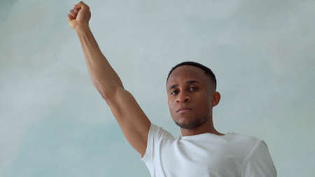 Close portrait of a black man with his fist raised up. Black lives matter