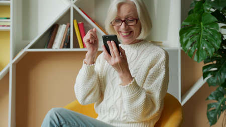 Elderly woman is sitting on the sofa, holding a smartphone, feeling very happy after receiving an SMS notification about the news. An elderly woman received a prize while holding a smartphone