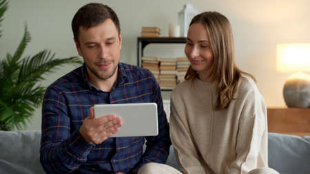 Excited happy family couple looking at digital tablet feel winners overjoyed by lottery winning bet bid, celebrate good internet news.