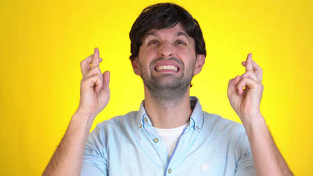 Young man look camera bit lips hands folded in prayer beg about something good keep fingers crossed making wish isolated on yellow background in studio. Stock fotó