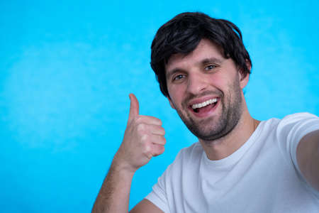Photo of handsome man in casual t-shirt and bristle on face smiling on camera with thumb up while taking selfie isolated over blue background
