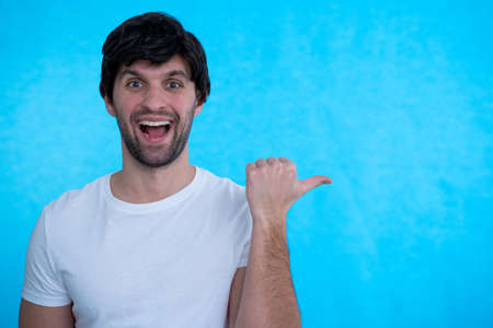 Cheerful young man, points with thumb aside, promots new item, smiles pleasantly, isolated over blue background