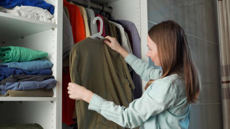 Young attractive woman chooses clothes in a wardrobe at home.