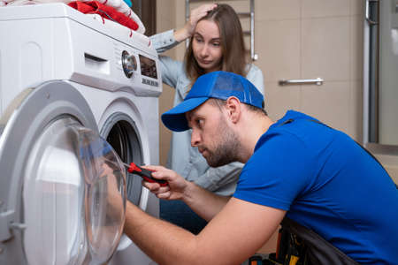 Repairman repairs a washing machine in front of a woman. A man communicates with the owner of a washing machine