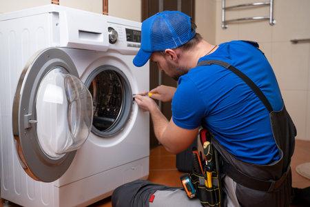 Working man plumber repairs a washing machine in home. Washing machine installation or repair. plumber connecting appliance