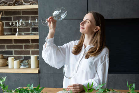 Woman takes a glass out of the dishwasher while standing in the kitchen Stock Photo