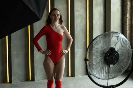 Young fashion model woman with perfect slim body posing in red bodysuit. Fashion studio shot.