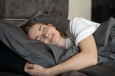 Relaxed woman in the bedroom, has pleasant dreams, keeps her eyes closed, enjoys a good rest at home Standard-Bild
