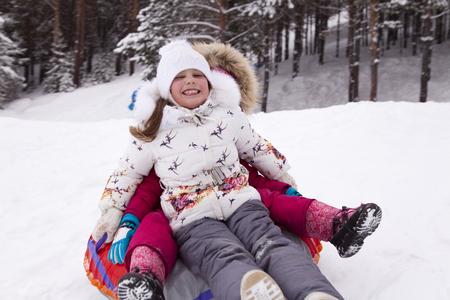 Šťastná holčička křičela s potěšením a válela se sněhem. Zimní zábava.
