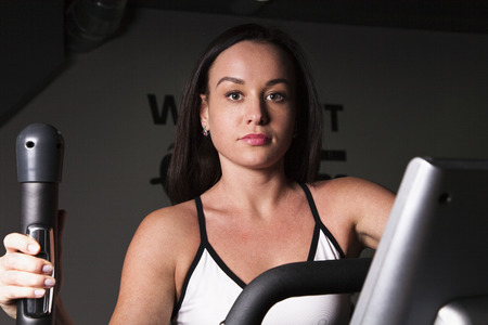 cardio workout: A young girl goes in for sports in the gym .Cardio workout. Stock Photo