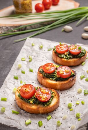 Sandwiches on toasted white bread with spinach cheese decorated with tomato slices. Selective focusing.