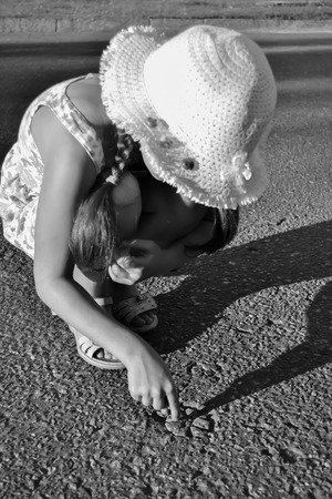 Young girl is painting the flower on the asphalt photo