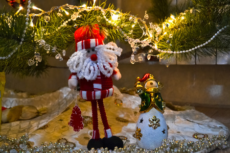 nosed: Santa Claus and snowman near the christmas tree amongst lights of garland
