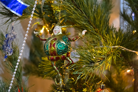figurine of jester on the christmas tree amongst lights and garland photo