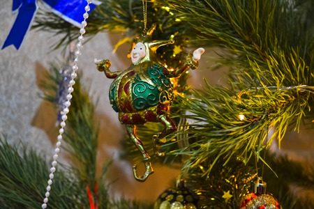 dacoration jester on the christmas tree amongst lights and garland photo