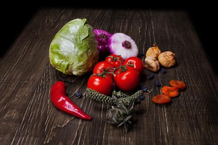 dried vegetables: Frescas Ingredientes de comida verduras en el tabel: tomate, repollo, higo, pasas, albaricoques secos, r�cula, cebolla