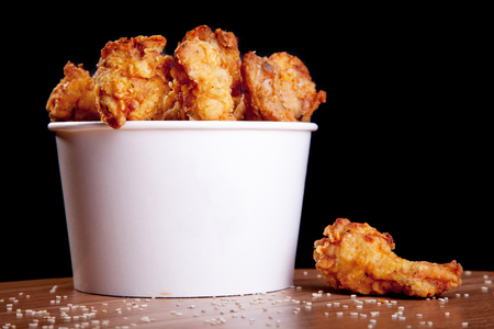 black wings: BBQ Chicken wings in a white bucket on a wooden table and black background.