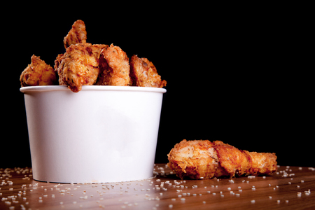 BBQ Chicken legs in a white bucket on a wooden table and black background.