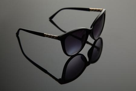 Fashion women sunglasses, black plastic, gold decoration on the douche, stylish gradient background with polarizing filter.