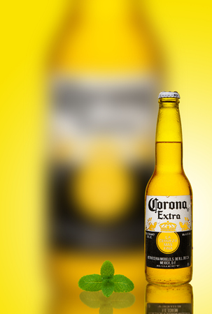 Los Angeles CA: Photo of a 12 ounce bottle of Corona Extra Beer. Water drops on a bottle. Corona is produced by Grupo Modelo with Anheuser Busch InBev. Yellow gradient background.