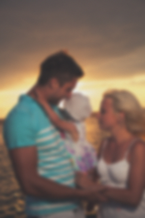 Blurred young family father mother and daughter at sunset on the lake. Very emotional moment.