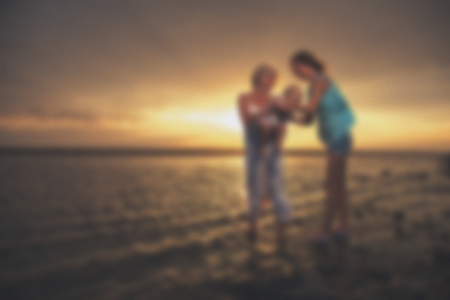 Blurred - young  family at sunset on the lake. Very emotional moment.