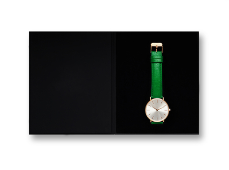 Classic women's gold watch with white dial, green leather strap, isolate on a white background. View from the top in the box. 免版税图像