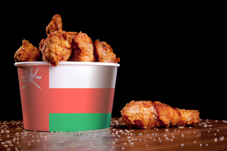 BBQ Chicken wings in bucket flag of Oman on a wooden table and black