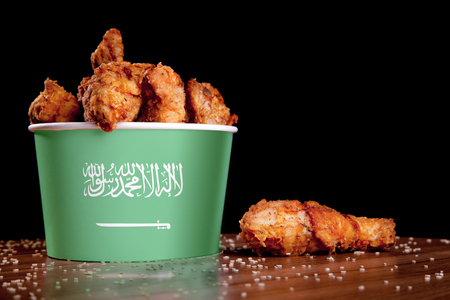 BBQ Chicken wings in bucket flag of Saudi Arabia on a wooden table and black Banque d'images