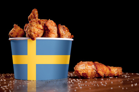 BBQ Chicken wings in bucket flag of Sweden on a wooden table and black Reklamní fotografie - 121024180