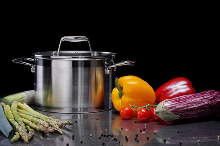 Metal saucepans in the kitchen with natural ingredients for making vegetarian soup.