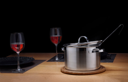 Metal saucepan with soup on a wooden table with two glasses of red wine.
