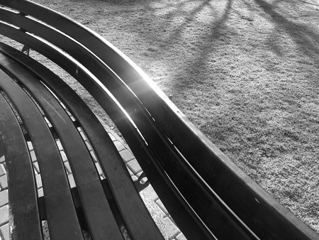 Pattern of geometric shapes on a street bench of wood on the lawn black and white