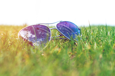 Soft focus, sunglasses on the green grass, blue sky reflections, summer mood.