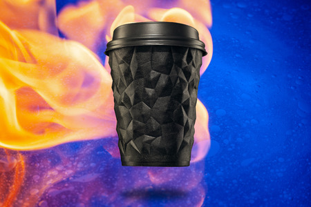 A cup of textured coffee geometry with a lid black against the fire.