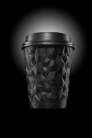 A cup of textured coffee geometry with a black lid is a good concept. Reklamní fotografie