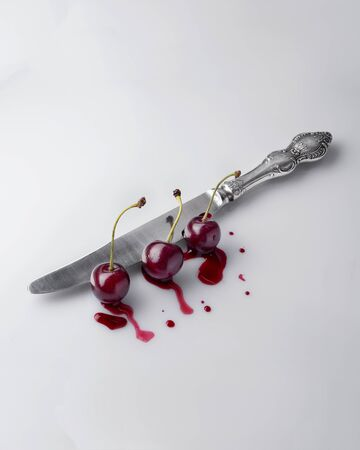 Natural cherry cuts the old knife oreginalny concept. View from the top and side. 免版税图像